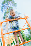 Smiling kid having fun at playground. Child doing gymnastic exercises Stock Images