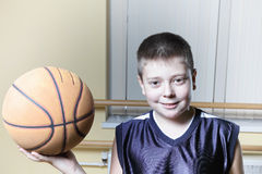 Smiling kid holding basketball Stock Photo