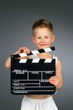 Smiling kid holding movie clapper board. Stock Photo