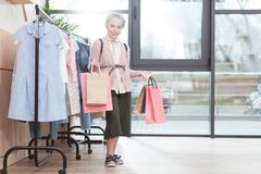 Smiling kid holding paper shoping bags in hands while standing near hanger. At shop stock photography