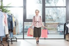 Smiling kid holding paper shoping bags in hands while standing surrounded by hangers. At shop royalty free stock images
