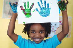 Smiling kid holding up his hands Stock Images