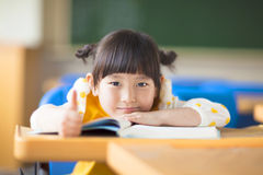 Smiling kid lie prone on a desk and thumb up. In a classroom Royalty Free Stock Images