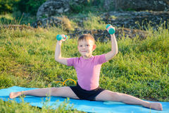 Smiling Kid Lifting Weights While Splitting Legs Stock Images