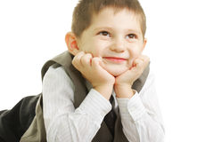 Smiling kid looking up. Laying down against white background Royalty Free Stock Photography