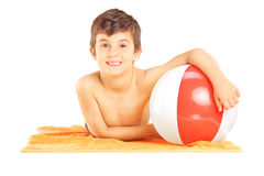 Smiling kid lying on a beach towel and holding a ball Stock Photo