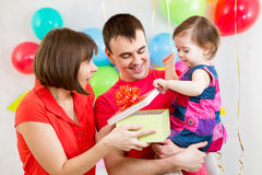 Smiling kid, mother and father opening gift box Royalty Free Stock Image