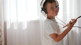 Smiling kid with phone into hands listening to music across headset and dancing in room