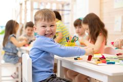 Smiling kid playing with colorful clay in kindergarten royalty free stock photos