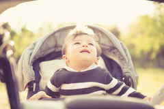 Smiling kid in pram looking up Royalty Free Stock Photos