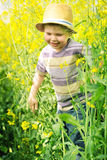 Smiling kid running among the canola flowers Royalty Free Stock Images