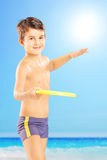 Smiling kid in shorts throwing frisbee on a beach next to the se. Smiling kid in swimming shorts throwing frisbee on a beach next to the sea Royalty Free Stock Photography