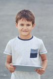Smiling kid with tablet computer. School, education, technology, leisure concept Royalty Free Stock Photography