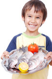 Smiling kid with three fresh fishes on table. Isolated on white Royalty Free Stock Image