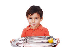 Smiling kid with three fresh fishes on table Royalty Free Stock Photos