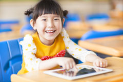 Smiling kid using tablet  or ipad. In a classroom Stock Photos