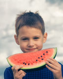 Smiling kid with watermelon against blue sky. Smiling boy with watermelon against blue sky Stock Photos