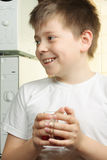 Smiling kid in white with tea Royalty Free Stock Image