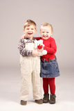 Smiling kids. Two kids laughing and holding teddy bear Royalty Free Stock Photos