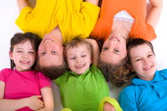 Smiling kids. Five caucasian happy smiling kids lying in a row on the floor stock photo