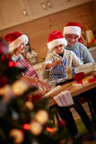 Smiling kids baking cookies with father on Christmas Royalty Free Stock Image