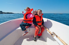 Smiling kids on the boat. Girl and boy sitting on the prow of the floating boat stock photo
