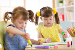 Smiling kids drawing together at hobby group indoors. Smiling adorable kids drawing together at hobby group indoors Royalty Free Stock Photography