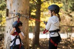 Kids enjoying zip line adventure on sunny day. Smiling kids enjoying zip line adventure on sunny day Stock Photos