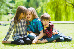 Smiling kids having fun at grass. Children playing outdoors in summer. teenagers communicate outdoor Royalty Free Stock Photography