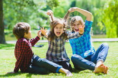 Smiling kids having fun at grass. Children playing outdoors in summer. teenagers communicate outdoor Stock Images