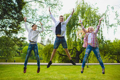 Smiling kids having fun and jumping at grass. Children playing outdoors in summer. teenagers communicate outdoor Royalty Free Stock Photos