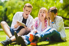 Smiling kids having fun and look to tablet at grass. Children playing outdoors in summer. teenagers communicate outdoor Stock Image