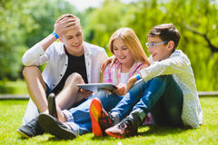 Smiling kids having fun and look to tablet at grass. Children playing outdoors in summer. teenagers communicate outdoor Royalty Free Stock Photos