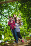 Smiling kids having fun at playground. Children playing outdoors in summer. Teenagers riding on a swing outside Stock Photo