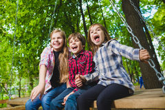Smiling kids having fun at playground. Children playing outdoors in summer. Teenagers riding on a swing outside Royalty Free Stock Photography