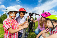 Smiling kids in helmets repair bike together Stock Images