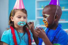 Smiling kids with icing on their faces Royalty Free Stock Image