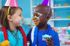 Smiling kids with icing on their faces Stock Photos