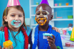 Smiling kids with icing on their faces Royalty Free Stock Photo