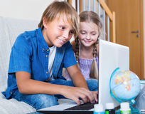 Smiling kids internet chatting on notebook Stock Images