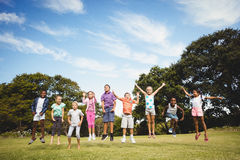 Smiling kids jumping together during a sunny day Stock Photo