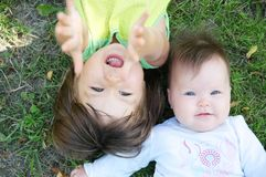 Smiling kids lying on grass in summer. Children: Toddler and baby portrait having fun. Little sisters. Happy childhood Royalty Free Stock Photo