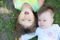 Smiling kids lying on grass in summer. Children: Toddler and baby portrait having fun. Little sisters. Happy childhood. Concept Stock Photos