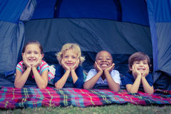 Smiling kids lying in the tent together Stock Images