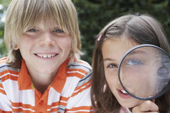 Smiling Kids With Magnifying Glass Royalty Free Stock Photography