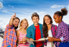 Smiling kids with map at city tours stand together Royalty Free Stock Image