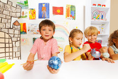 Smiling kids paint New Year balls for Xmas tree