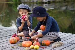 Smiling kids paint small Halloween pumpkins. On the river bank Royalty Free Stock Photo
