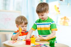 Smiling kids play and paint at home or Stock Photos