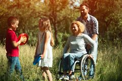 Smiling kids play with their disabled young mother stock photo